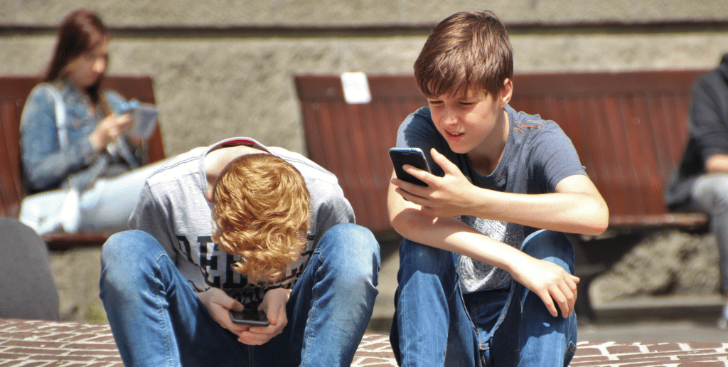 Content-Fotos_Small_0031_2-boy-sitting-on-brown-floor-while-using-their-smartphone-159395